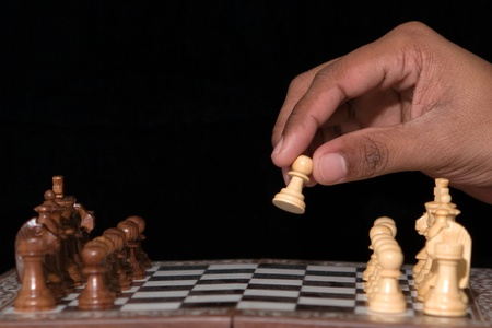 Hand moving a pawn as first move photo