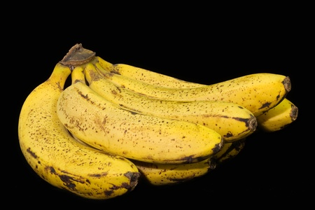 Bunch of speckled bananas isolated against black background Stock Photo - 8561378