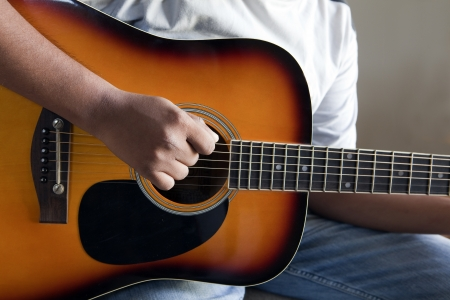 closeup view of right hand strumming an acoustic guitar photo