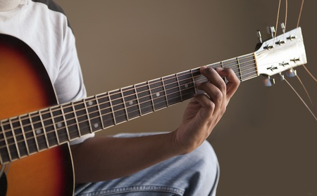 closeup view of left hand playing guitar - fretboard photo