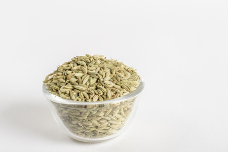 fennel seeds: Glass bowl with fennel seeds on a white background