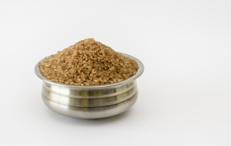 Steel container filled with parboiled Kerala Matta rice on a white background