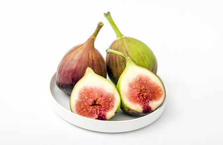 Fresh whole and cut figs on a white background