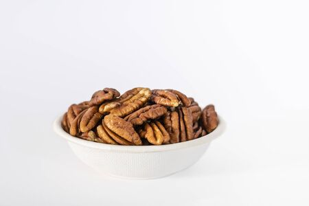 Bowl of Pecan nuts (Carya illinoinensis) on a white background
