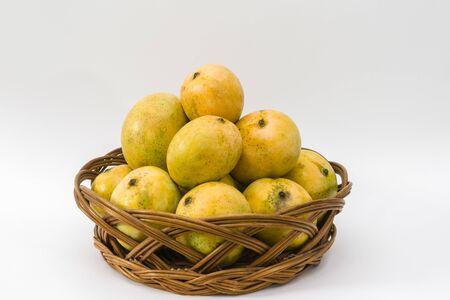 A basket of Moovandan mangoes (Mangifera indica) on a white background