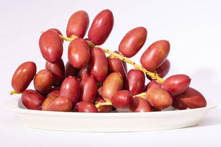 Fresh red date fruits (Phoenix dactylifera) in a dish. 写真素材