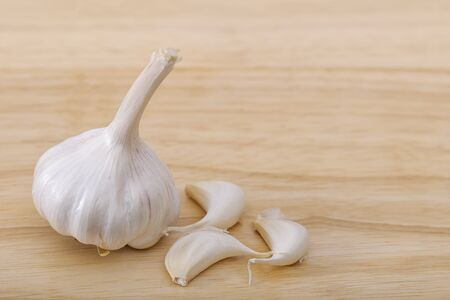 Closeup view of Garlic bulb and cloves on a wooden board.