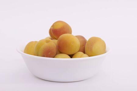 A bowl of ripe apricot (Prunus armeniaca) fruits on a white background