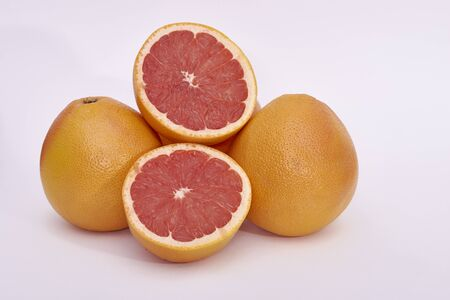 Pink grapefruits - whole and cut - on a white background