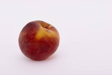 Single ripe peach fruit on a white background