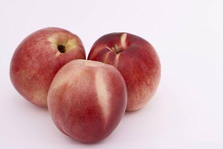 Three ripe peaches on a white background