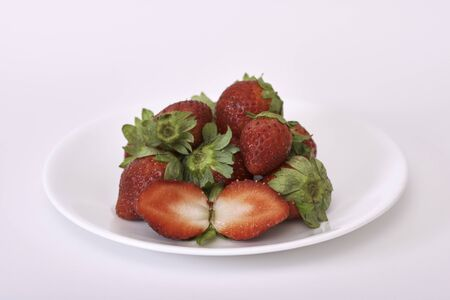 A plate of ripe whole and sliced strawberries on a white background