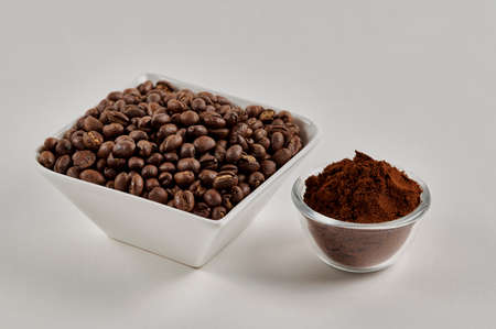 Roasted whole peaberry coffee beans and freshly ground coffee powder on a white background