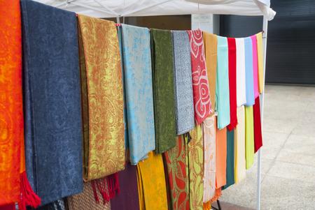 street vendor: Street vendor displays variety of colorful fabrics Stock Photo