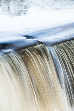 spillway: Dimple forms in water pouring over spillway Stock Photo