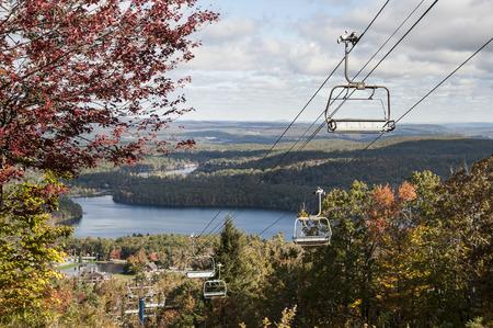 スキー場のリフトのカットの丘と池のパノラマ ビューを提供します