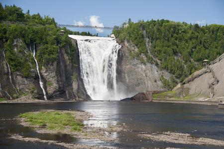 川で漁師が小人症のモンモランシーの滝の壮大な高さで 写真素材