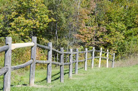 dropoff: Ragged, repaired fence meanders across edge of drop-off Stock Photo