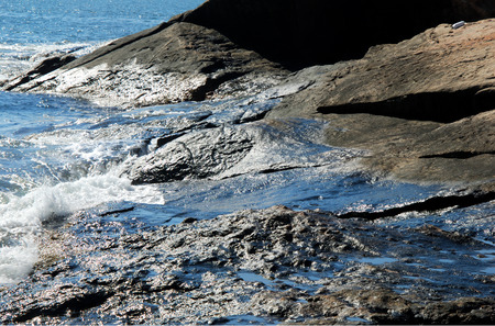 the residue: Years of oil residue glisten in the morning sun on wet rocks at Hazard Rock in Narragansett, Rhode Island