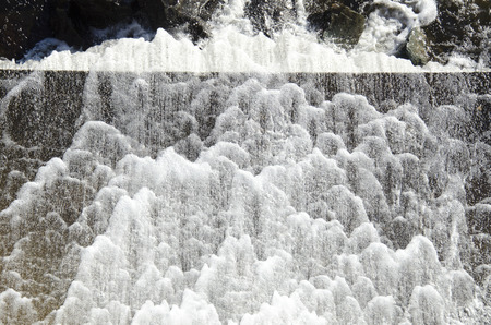 spillway: Water rushing off dam, creating a scalloped pattern of foam