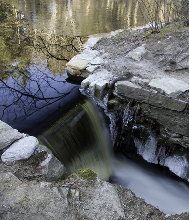 ice dam: Ice builds around small dam as temperature drops Stock Photo