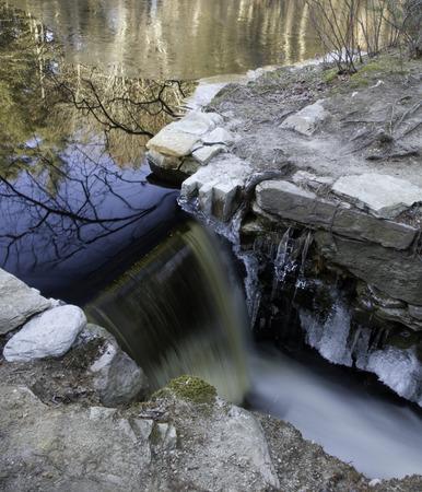 ice dam: Ice builds around small dam as temperature drops Stock Photo