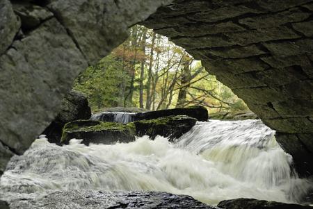 rushing water: Water rushing under stone bridge Stock Photo
