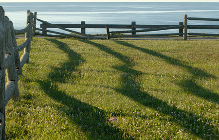 日の出フェンスの影 写真素材