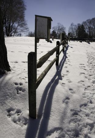Sporen van bezoekers op een begraafplaats op een heldere dag na een sneeuwval Stockfoto