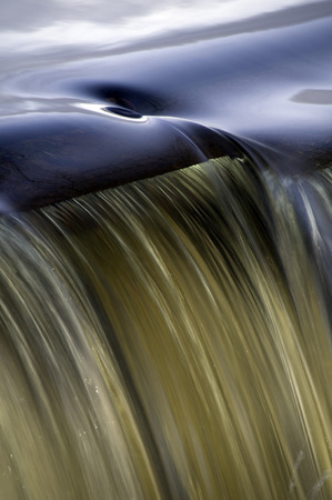 Whirlpool forms at the edge of a small waterfall