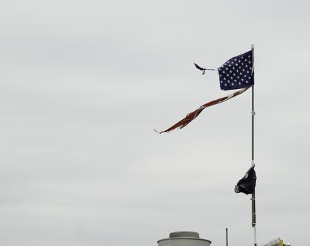 뻣뻣한 산들 바람은 코니 아일랜드에서 깃발의 유적을 채찍질합니다.