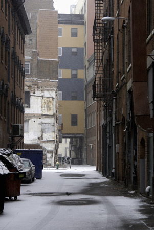 back alley: Snow starts to mount up on urban back alley Stock Photo