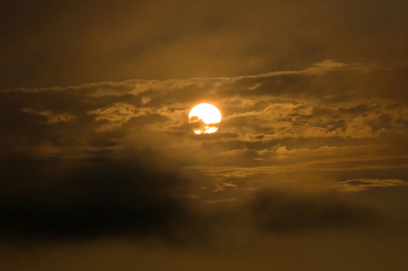 room for text: The sun is visible on an orangeblack background and foreground with clouds and room for text. Stock Photo