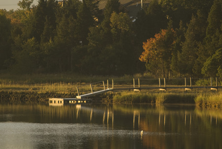 inlet bay: Dock reflecting in river at sunrise Stock Photo