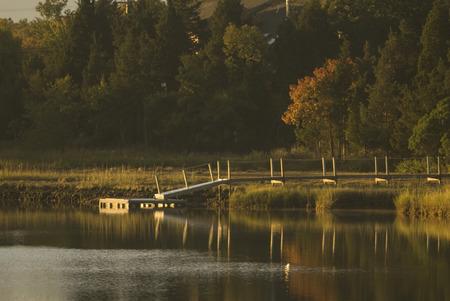 Dock reflecting in river at sunrise Banco de Imagens