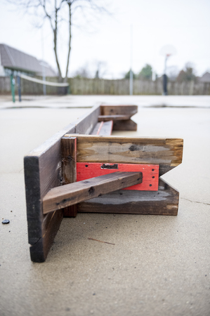 suggests: Overturned bench on a rainy fall day suggests end of tennis season