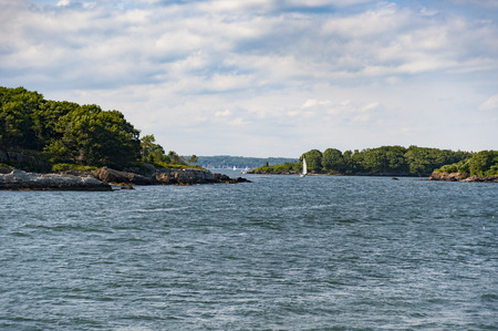 Sailboat wends its way past islands on Casco Bay in Maine