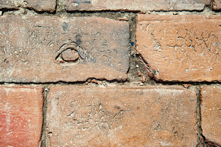 Old brick has unusual knot on its rough surface Stock fotó