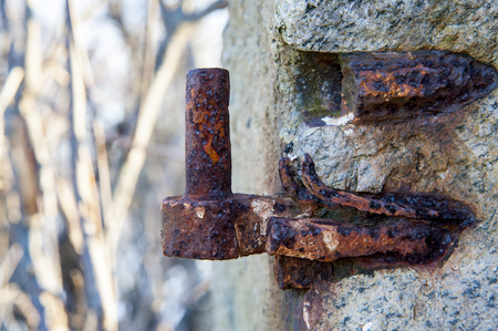 hinge: Rusted, pitted hinge all that remains of gate in stone wall Stock Photo