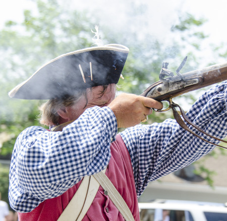 musket: BRISTOL, RHODE ISLAND - JULY 4, 2011:  Revolutionary War reenactor fires his musket in Fourth of July parade in Bristol, Rhode Island, an annual tradition since 1785 Editorial