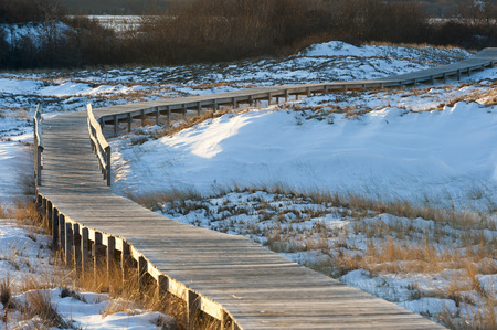 meanders: Boardwalk meanders across snow-covered sand dunes Stock Photo