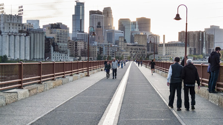 MINNEAPOLIS, MINNESOTA - OCTOBER 10, 2015:  Walking the Stone Arch Bridge over the Mississippi River on Saturday evening
