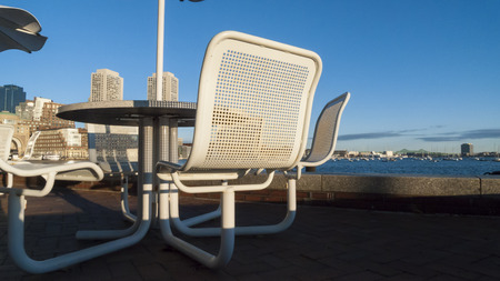 unoccupied: Unoccupied tables along Boston Harborwalk on winter morning Stock Photo