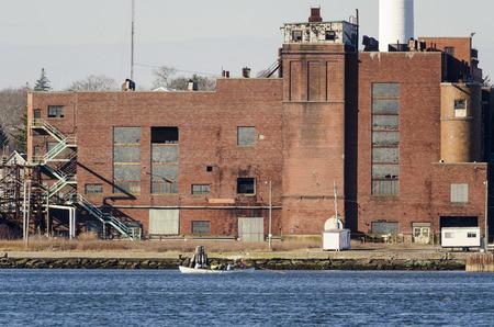 NEW BEDFORD, MASSACHUSETTS - FEBRUARY 17, 2016: Winter sun lighting up abandoned factory on Acushnet River in New Bedford, Massachusetts Redakční