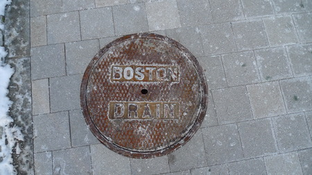 manhole: BOSTON, MASSACHUSETTS - JANUARY 21, 2016: Rusty manhole cover holding out against winter snow and salt