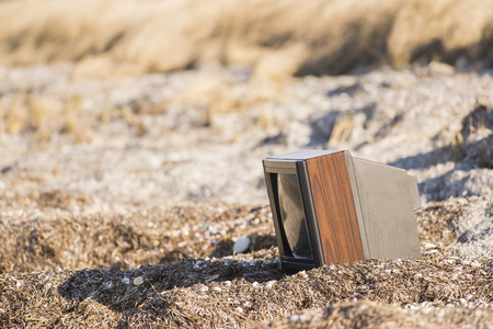 trashed: Old television dumped on empty stretch of beach Stock Photo