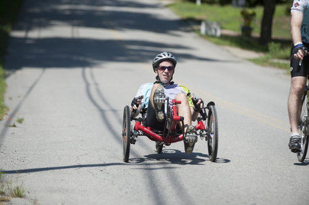 cancer research: DIGHTON, MASSACHUSETTS, AUGUST 7, 2010: Rider on a recumbent tricycle enjoys a short downhill in Pan-Mass Challenge charity ride for cancer research and patient care at Dana-Farber Cancer Institute