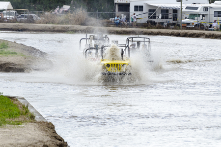 NAPLES, FLORIDAUSA - MARCH 3, 2012: Swamp buggy Jeep pushes rooster tail directly into cockpit
