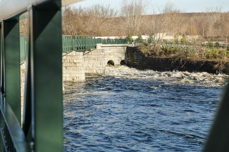bikeway: Water races under footbridge on Blackstone River Bikeway in Lincoln, Rhode Island