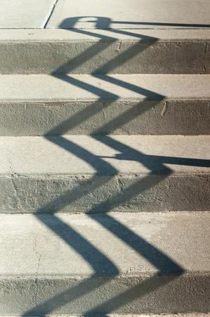 concrete steps: Shadow of railing zigzags up concrete steps